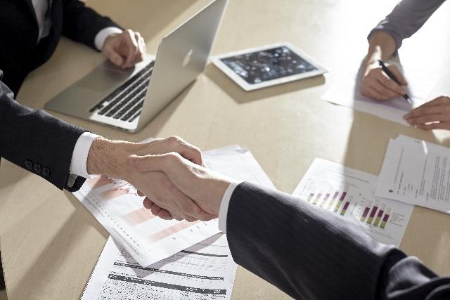 PCと書類が置かれたテーブルの上の握手
