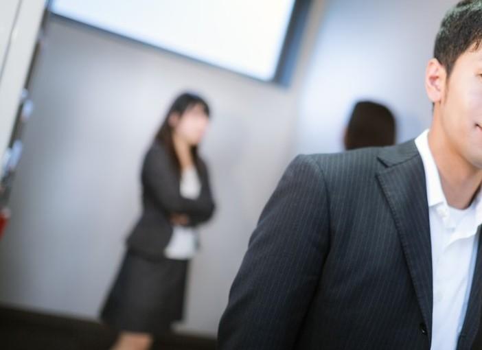 廊下で立ち話する2人の女性と聞き耳を立てる男性